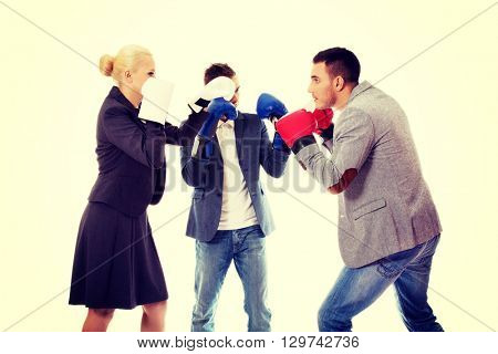 Three business people wearing boxing gloves start competition fight