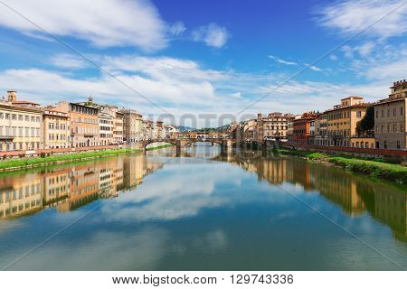famous Triniti and  Ponte Vecchio bridges reflecting in river Arno at summer day, Florence, Italy