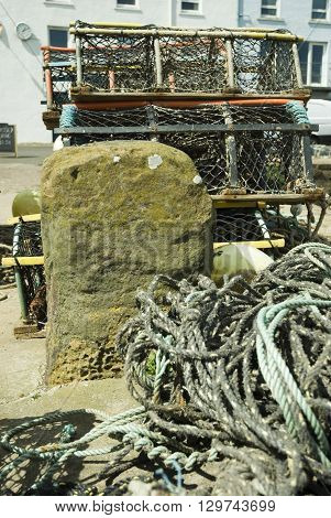 an image of fishing pots and nets on the harbour beside a stone capstan