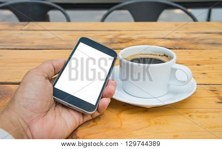White display smart phone in handWhite coffee cup placed on wooden floor.