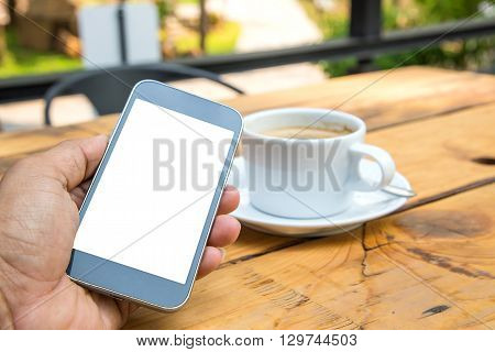 Black display smart phone in handWhite coffee cup placed on wooden floor.