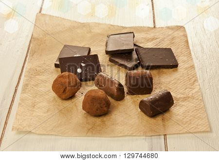 Chocolate bonbons and pieces on a piece of cooking paper with a blurred background with bokehs on a piece of brown cooking paper on a light colored wooden texture
