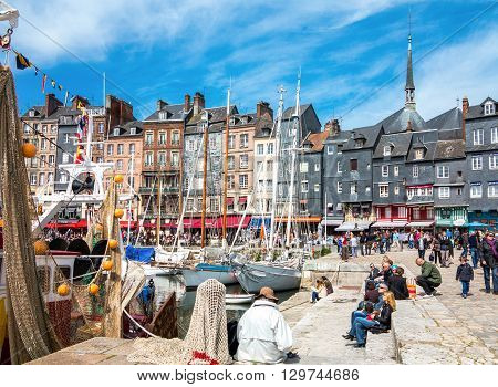 Honfleur France - May 19 2012: Normandy tourists traditional houses and boats in the old harbor basin.