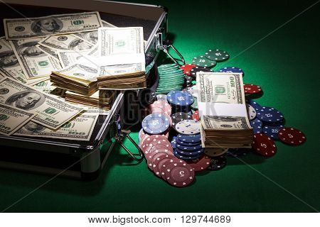 Open case with dollars and chips on a green cloth background