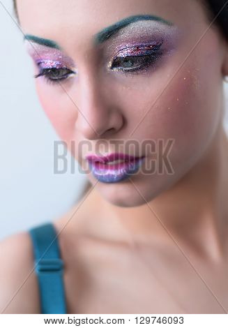 Beautiful girl with bright creative colorful fashion makeup. Blue eyebrows, glitter eyeshadows and two color - blue and pink - gradient lips