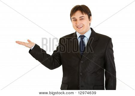 Smiling young businessman presenting something on empty hand isolated on white