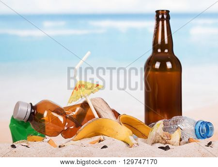 Bottles, cigarette butts and other debris in the sand on the seashore.