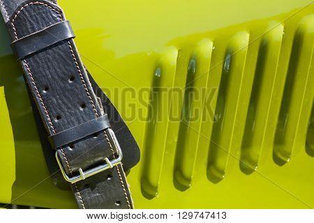 Vintage leather belt securing a car's hood.