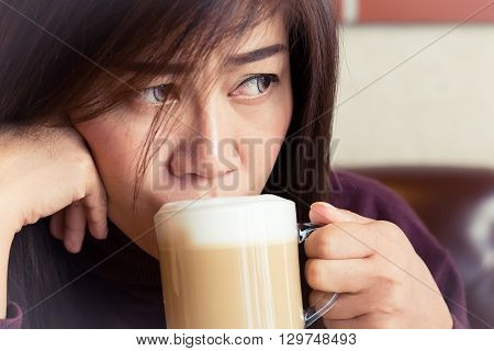 woman drinking a coffee latte in cafe restaurant