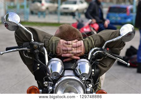 Motorcyclist resting on his bike at the opening of the summer season