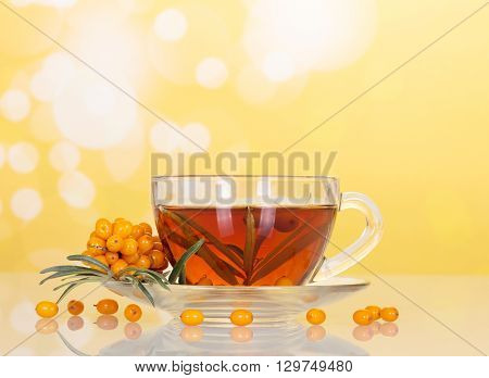 Bunch of sea buckthorn and cup with beverage from her abstract yellow background.