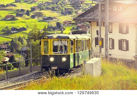 Grindelwald Switzerland - July 07 2012: Passenger train arrives from Kleine Scheidegg at sunset.
