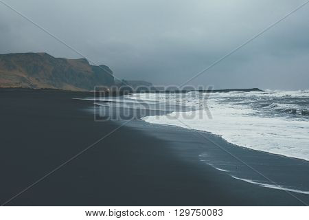 Bad weather on Vik beach, Iceland. Storm with waves on black beach coastline.