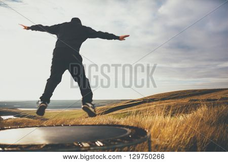 Out of focus man jumping on trampoline in Iceland. Concept of freedom and loneliness.