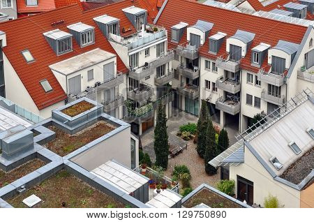 WURZBURG, GERMANY - APRIL 18 2016: The courtyard of a modern apartment house with balconies tiled and green roofs and plants. Look down.