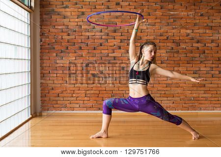 Woman dancing with a hula hoop in a beautiful studio