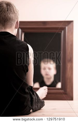 Child Sitting On Floor Staring Into Mirror
