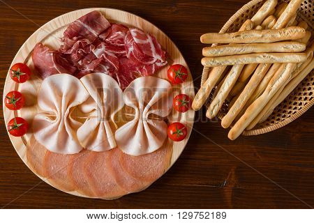 Italian cutting board and breadsticks on a wicker basket seen from above