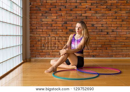 Woman sitting with a hula hoop in a beautiful studio