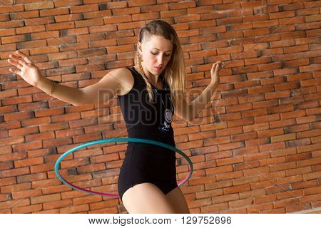 Woman practicing with a hula hoop on a brick wall background