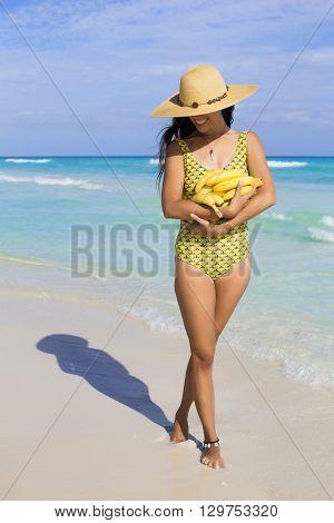 Young woman holding lots of bananas at the beach. Playa del Carmen, Mexico.
