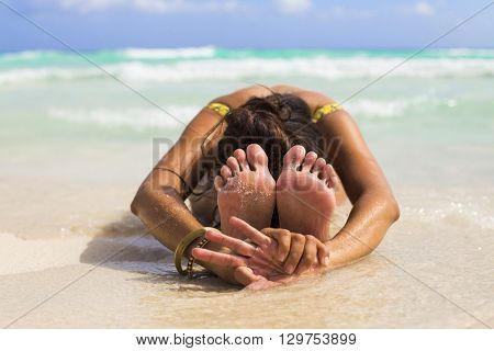 Woman practicing yoga at the beach. Child's pose, balasana in Sanskrit.
