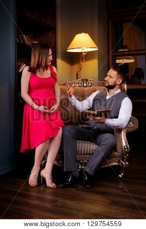 Man reads verses to the girl in the room. Pregnant woman listens attentively