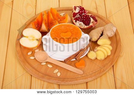 A cup of pumpkin puree, chopped ginger, pomegranate grains on a background of light wood.