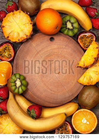 tropical fruits: pineapple oranges bananas passion fruit strawberry kiwi fruit with empty space (top view)