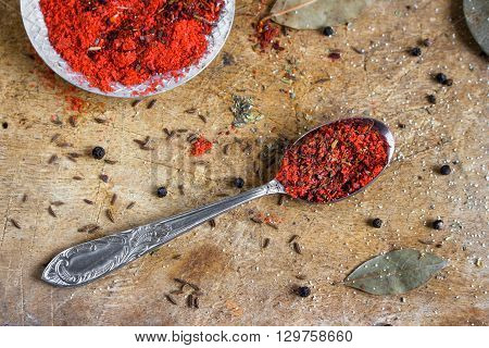 red spice mixture on the spoon and a plate on a wooden background