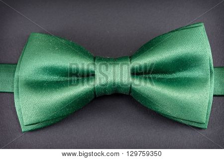 Green bow tie on dark wooden background