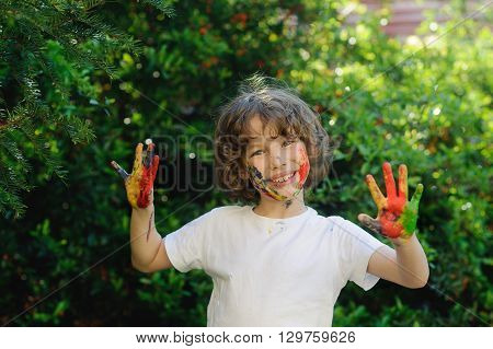 Child himself dirty in the paint and show his dirty hands into the camera. Cild has fun and painting and drawing. Children's creativity. Art for baby. Emotions. Delight.
