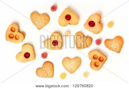 Brightly lit heart-shaped tea cookies and gum drops on white background