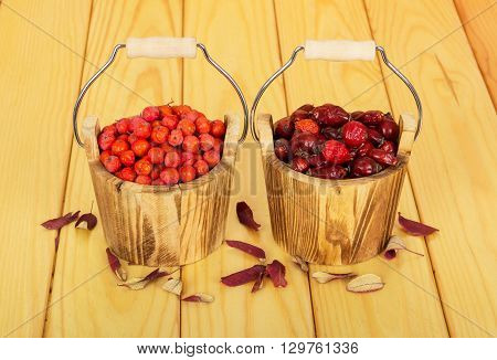 Buckets filled with rosehip and rowan berries on a background of light wood.
