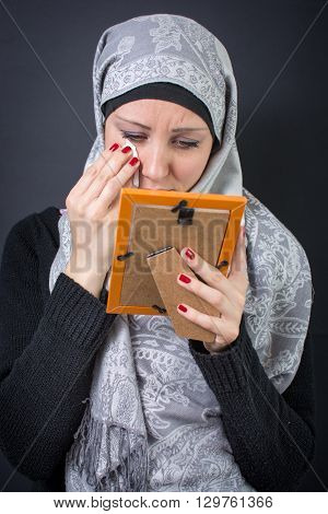 Muslim woman moaning over an old photograph in a frame