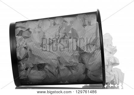 An overturned basket full of waste paper isolated on white background.