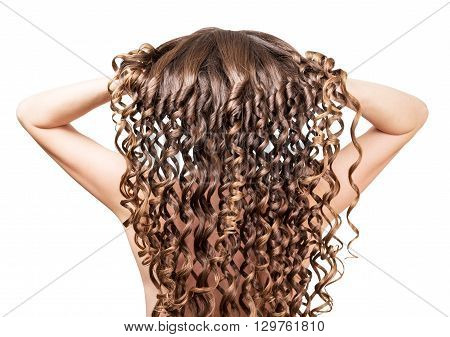 The girl straightens her arms long curly hair isolated on white background.