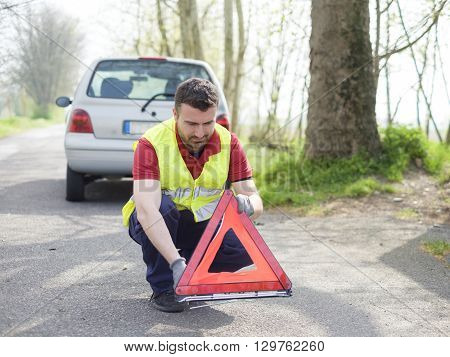 vehicle breakdown  and man with red triangle