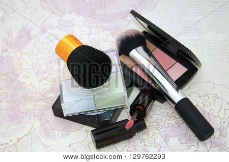 Loose Powder And Blushes And Lipgloss On Flower Background