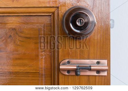 door knob and keyhole on wooden door close up image