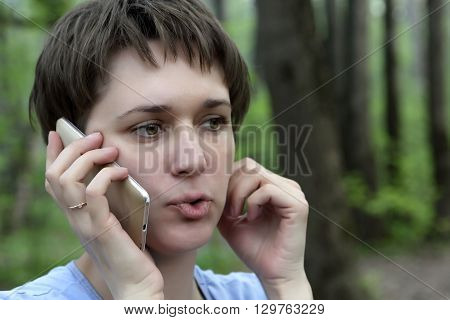 Woman talking on the phone in a park