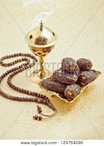 Aromatic oud burning in the burner, placed along with sweet arabian dates and islamic prayer beads. Muslim religious objects.