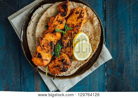 Delicious boneless chicken kebab on skewer served on arabic pita bread.
