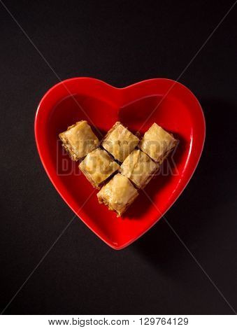 Popular middle eastern dessert - Paklawa in a red heart shaped dish. Unhealthy food concept.