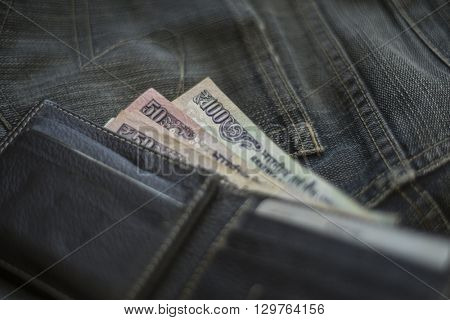 Hundred Indian rupee currency notes placed near wallet on jeans pocket.