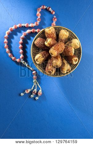 Bowl of scared Arabian date fruits with Islamic prayer beads on bright blue background.