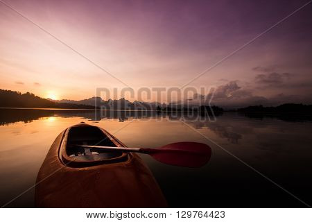 Red canoe boat on the lake with beautiful sunset scene