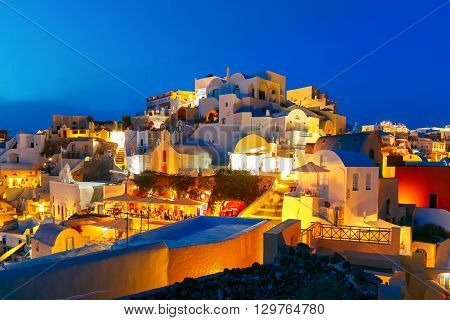 Old Town of Oia on the island Santorini, white houses and church with blue domes during twilight blue hour, Greece