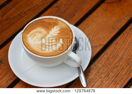 Close up of cappuccino coffee in wooden table