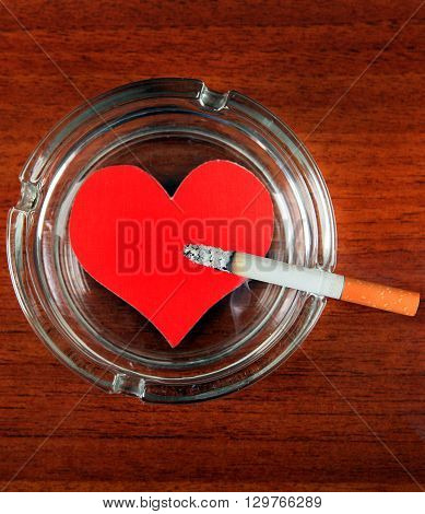Cigarette in Ashtray with Heart Shape on the Table